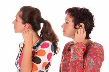 Two woman putting hearing aid into ear