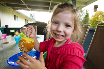 child eating caramel apple