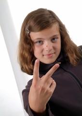 Ein Mädchen zeigt mit den Fingern Victory Zeichen