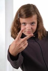 Ein junges Mädchen zeigt mit den Fingern Victory Zeichen.