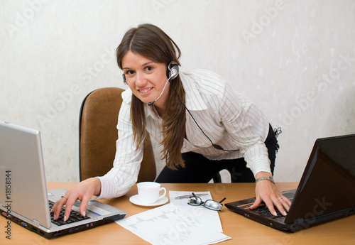 Quick smart girl at the office desk with laptops