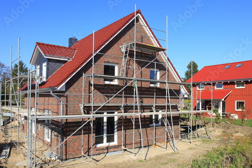 Neubau Einfamilienhaus Baugerüst Rohbau blauer Himmel