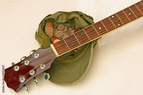 cap full of coins and guitar