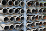 many stacked drain pipes on a construction site poster