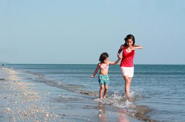 girls running along the beach