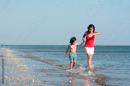 girls running along the beach