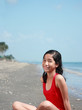 portrait of a young asian lady sitting at the beach