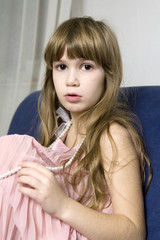 little cute upset girl sitting on sofa