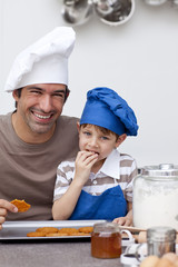 Father and son eating home-made cookies