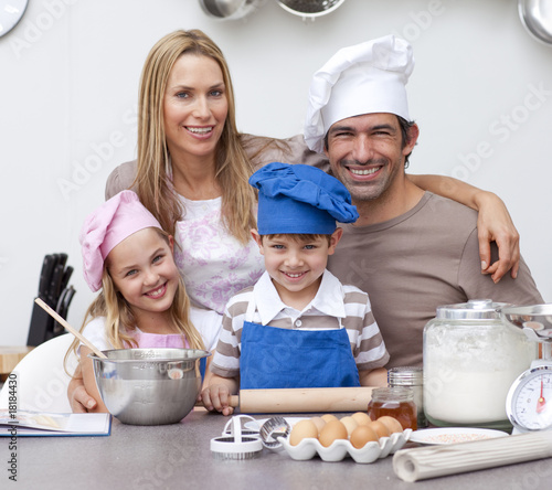Smiling parents helping children baking in the kitchen