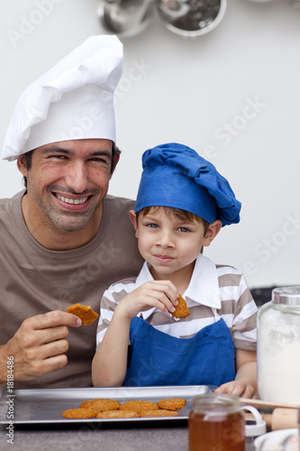 Father and son eating biscuits in the kitchen