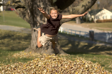 Girl Jumping into Autumn Leaves