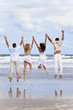 Four Young People, Two Couples, Jumping in Celebration On Beach