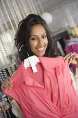 woman selects pink sleeveless top in retail store