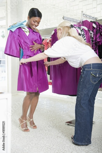 assistant helps woman consider fuscia raincoat