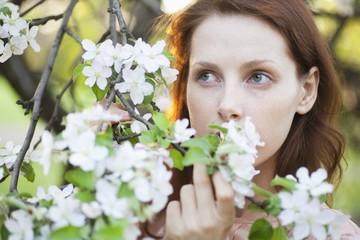 Redhead holds blossom