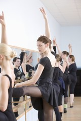 Young women practise ballet at the barre