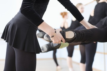Ballet teacher adjusts foot positions at the barre