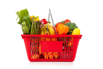Red shopping basket with vegetables on white