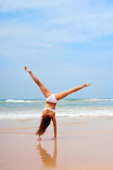 woman doing cartwheel at the beach
