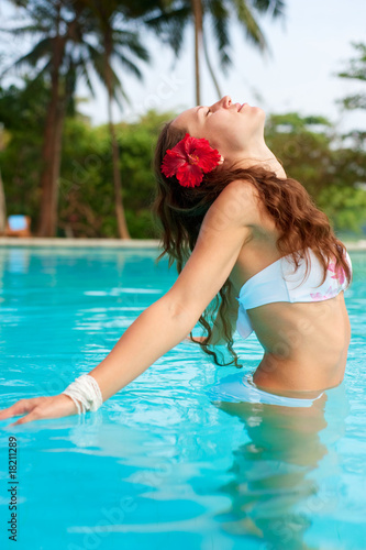 woman with red flower in the pool