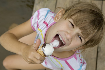 Little girl to screw up one's eyeswith ice-cream