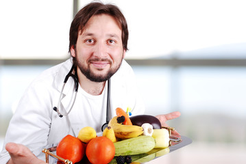 Young doctor in hospital with plenty of fruits and vegetables