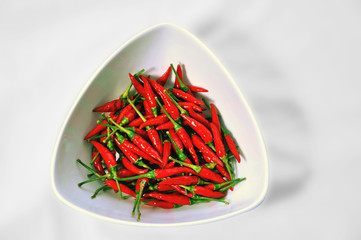 Bunch of red hot chillies peppers in a white bowl