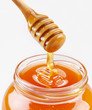Honey dipper and full honey pot isolated on a white background