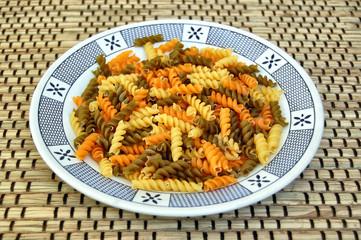 Three different flavors of raw fusilli pasta. Italian food.