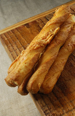 crispy cheese straws on a rustic wooden board