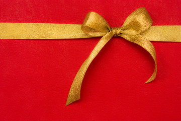 golden gift ribbon and bow on red background. some other you may