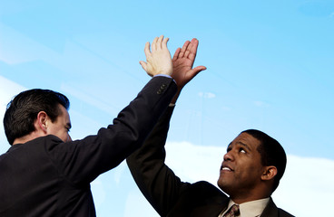 Two businessman giving each other high five