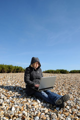 Girl with laptop on beach