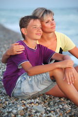 young woman embraces smiling boy on beach in evening