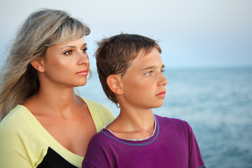 boy and young woman on beach in evening, Looking afar
