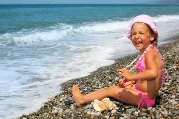 pretty little girl with seashell and necklace on stone seacoast