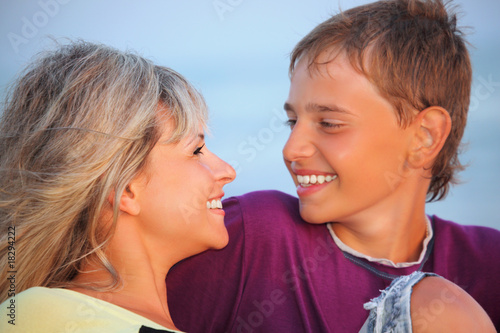 smiling boy and young woman on beach in evening, Looking against