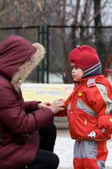 Mum helps the little girl to clasp red winter overalls