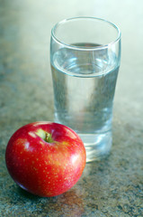 Glass of water and a ripe apple
