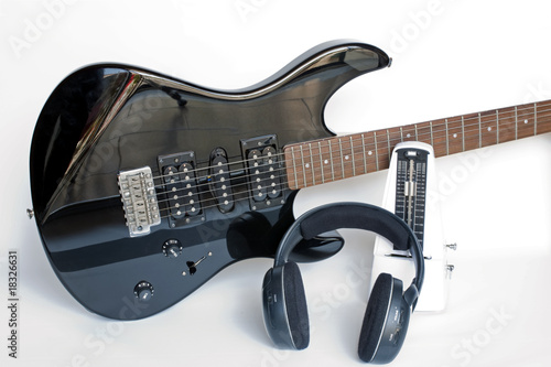 Black electric Guitar with metronome and headphone over white