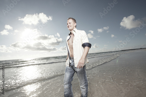 Handsome man walking down the beach