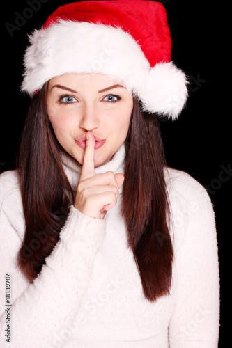 Pretty woman wearing santa hat saying shh