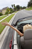 Young Woman Driving Convertible Car With Hand In The Air poster