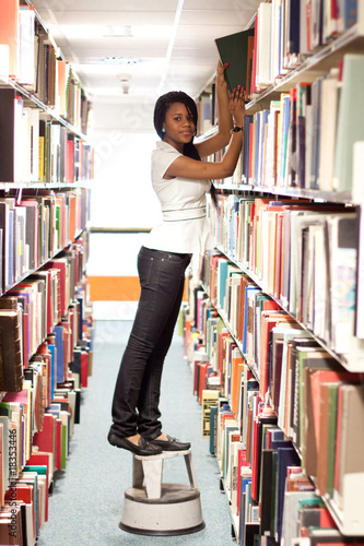 Teenage girl looking for a book in the library