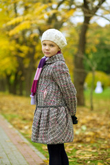 young small pretty girl in white beret in wonderful autumn park