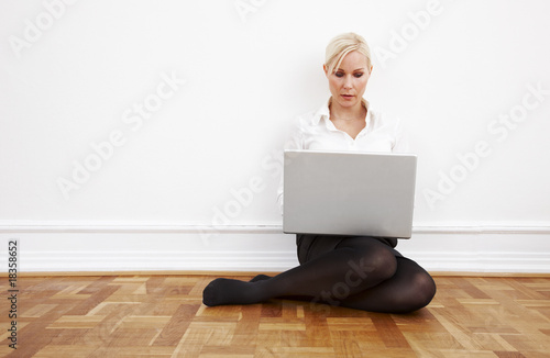 Blond businesswoman sitting on the floor with laptop