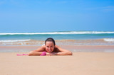 pleasant woman lying on the sand poster