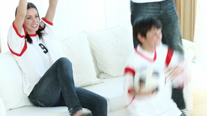 Family in Living Room watching Sport of TV