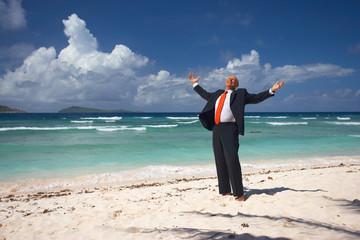 thankful businessman on sandy beach